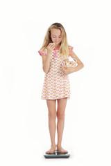 jeune fille se pesant avec paquet de sucreries