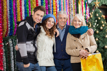 Family Standing Against Tinsels At Christmas Store