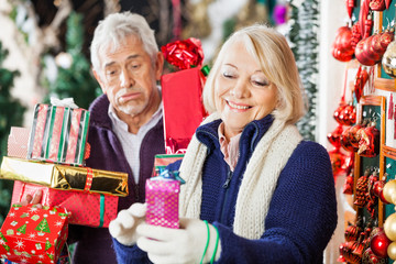 Woman Shopping With Tired Man Holding Presents In Store