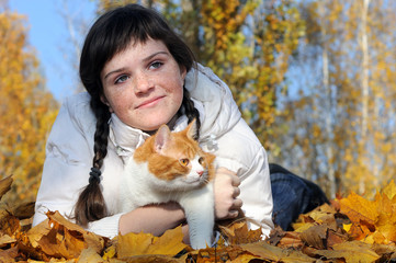 freckled teenage girl and cat relaxing in the  park