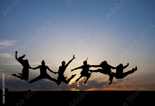 silhouette of friends jumping in sunset