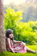 Smiling little asian girl sitting under a tree