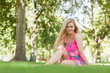 Content blonde woman sitting in a park