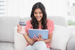 Smiling cute brunette sitting on couch holding credit card and t