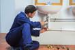 Handsome plumber repairing sink