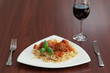 Front view of spaghetti and meatballs with red wine