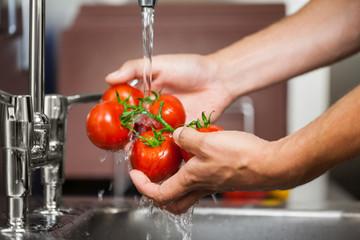 Kitchen porter washing tomatoes