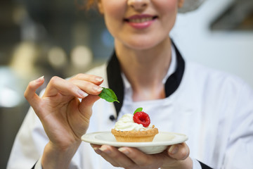 Happy head chef putting mint leaf on little cake on plate