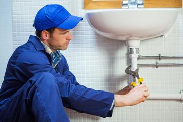 Attractive focused plumber repairing sink