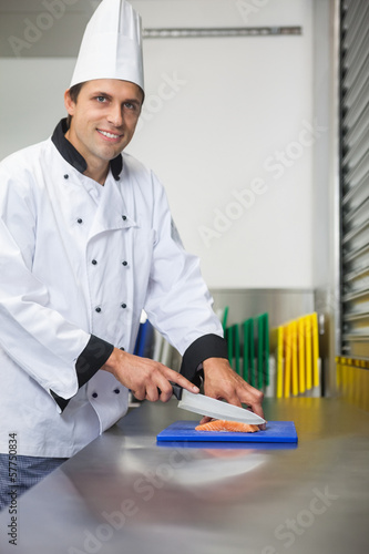 Smiling chef cutting raw salmon with knife on blue cutting board