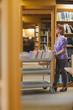 Serious female librarian pushing a cart