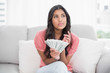 Thoughtful cute brunette sitting on couch holding money