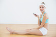 Content sporty woman holding her smartphone while sitting on the