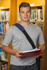 Handsome smiling student holding folder and notebooks