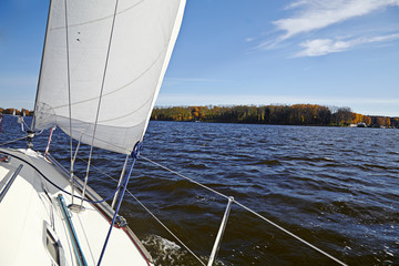 Yacht. Sailing on the lake in autumn sunny day. Luxury Lifestyle