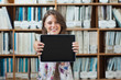 Female student against bookshelf holding out tablet PC in librar