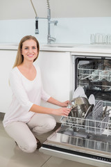 Lucky gorgeous model kneeling next to dish washer