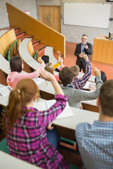 Students raising hands with a teacher in the lecture hall