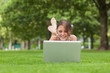Woman lying on grass and using laptop at the park