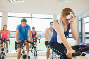 Tired people working out at spinning class