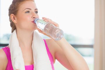 Woman drinking water in fitness studio