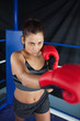 Determined young woman in red boxing gloves