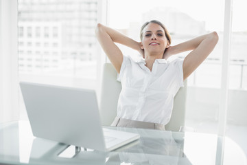 Relaxing classy businesswoman sitting on her swivel chair