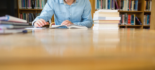 Mid section of a student studying at library desk