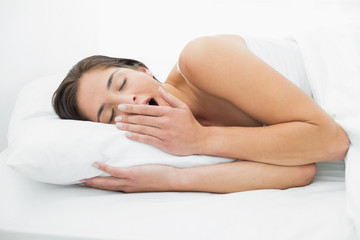 Young woman yawning in bed