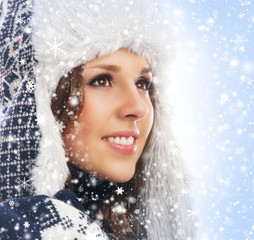 Portrait of a young woman in a winter hat on a snowy background
