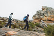 Couple walking through rocky landscape with trekking poles again