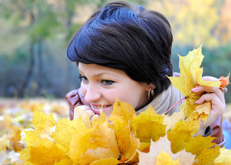 Girl in autumn with maple leaves