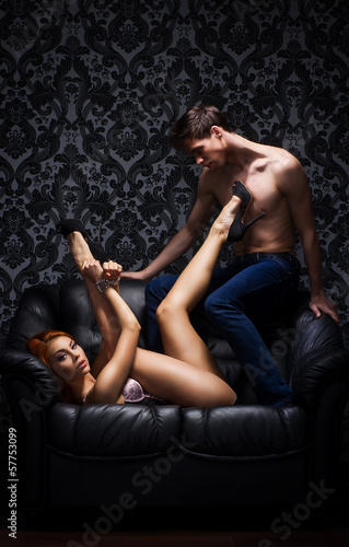 A young and beautiful couple on the leather sofa