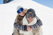 Man piggybacking woman in ski goggles against snow
