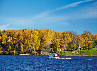 power boat on an autumn lake in sunny day