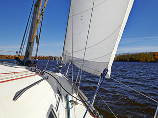 Yacht sailing on the lake in sunny autumn day