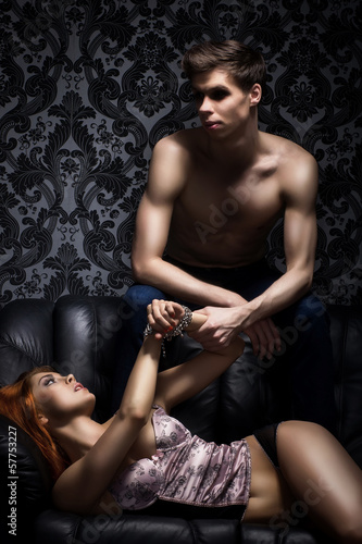 A young couple in bdsm action on a leather sofa