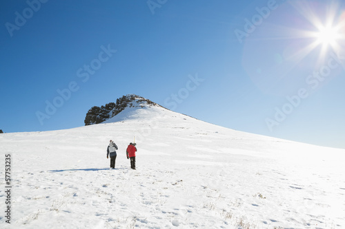 Skiers walking on snow on a sunny day