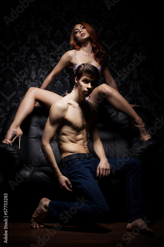A young and beautiful couple posing on the leather sofa