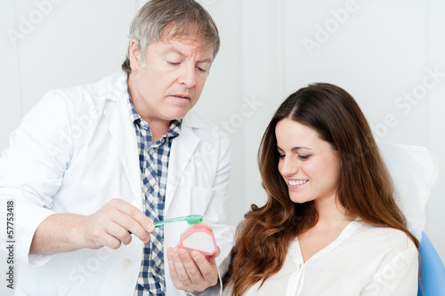 Dentist teaching patient how to clean her teeth