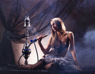 A sexy woman in luxury underwear smoking a hookah