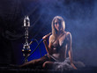 A sexy blond woman in luxury underwear smoking a hookah