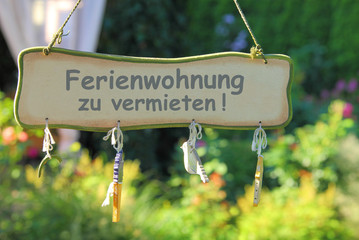 Ferienwohnung zu vermieten! - auf Schild im Gartenbereich