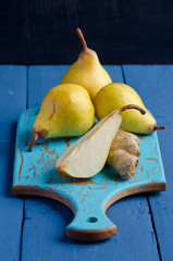 Yellow pears on a blue wooden board
