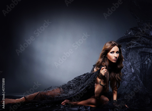 A young and beautiful woman in blowing silk on a dark background