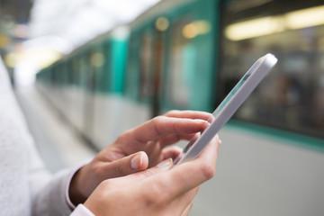 Woman using her Mobile phone on subway platform