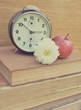 Vintage old clock and flower on books