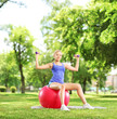 Female athlete in a park sitting on a ball and exercising