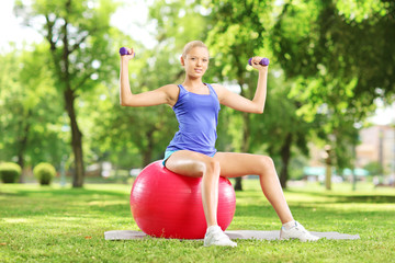 Female athlete in a park sitting on a ball exercising