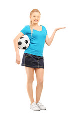 Young female holding a soccer ball and gesturing